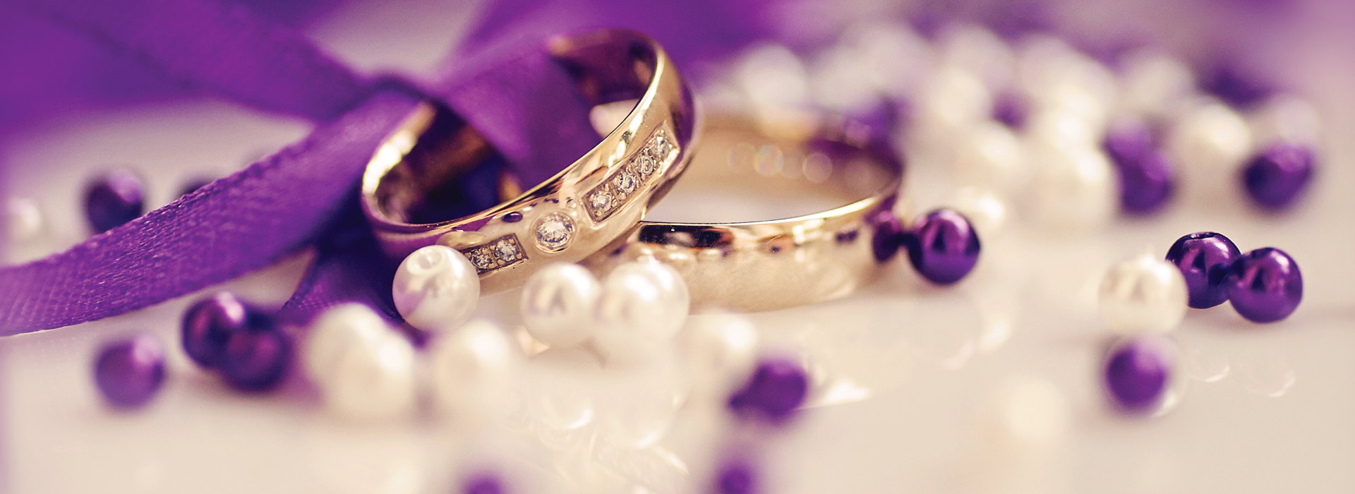 Two wedding rings in a purple background