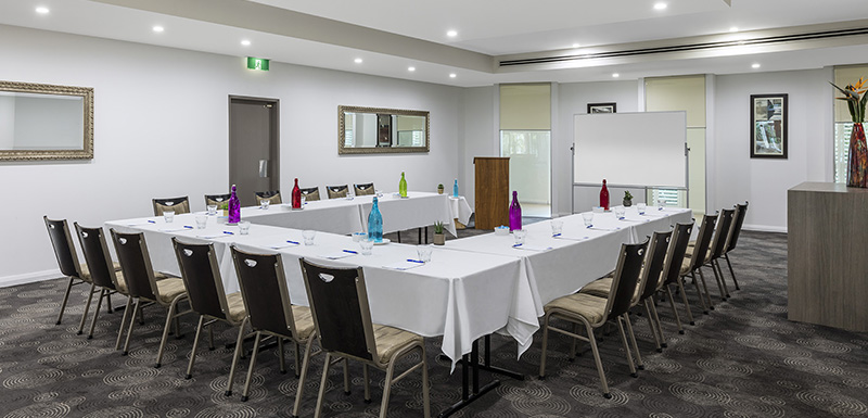 table and chairs set up in large meeting room for hire at port stephens hotel