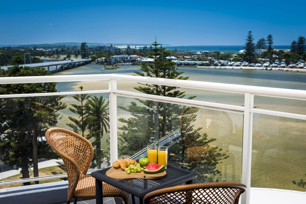Central Coast hotels with view of ocean from hotel studio apartment sunny balcony with chairs and full breakfast on table