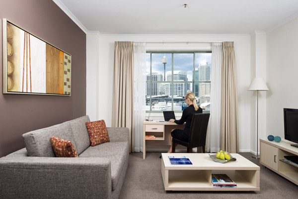 Hotels near Darling Harbour with corporate traveller visiting Sydney looking at view of CBD out of hotel apartment window