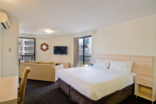 spacious modern hotel bedroom with views of Sydney city at Oaks Hyde Park Plaza