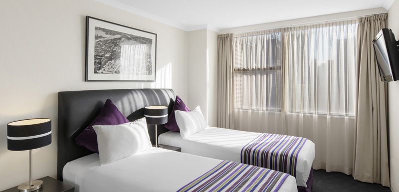 two single beds in 2 bedroom apartment with flat screen TV at Oaks Hyde Park Plaza hotel in Sydney