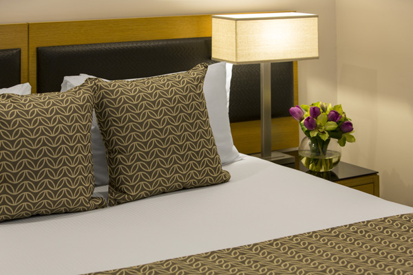 close-up of clean and comfortable queen size hotel bed with fresh pillows and side tables at Oaks Elan Darwin, Northern Territory