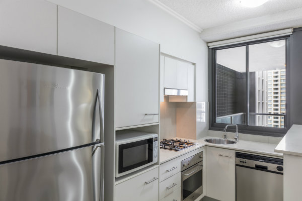 modern kitchen with large fridge, microwave, oven and dishwasher in 1 bedroom apartment at Oaks 212 Margaret St hotel, Brisbane, Queensland, Australia