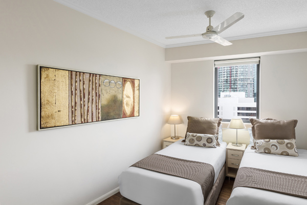 second bedroom with 2 single beds and ceiling fan in Brisbane CBD hotel