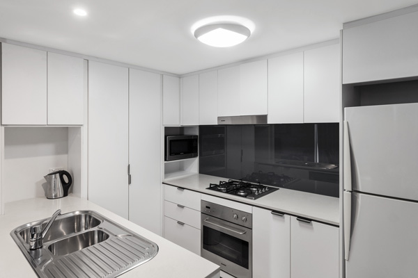 modern kitchen with large fridge, microwave and kettle at Oaks Festival Towers hotel on Albert Street in Brisbane CBD