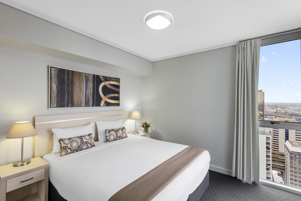 queen size bed in 1 bedroom executive apartment with views of Brisbane city at Oaks Festival Towers hotel on Albert St