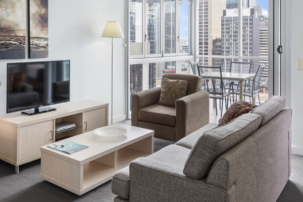 living room with comfortable couches and television in 1 bedroom hotel apartment near Central train station in Brisbane city