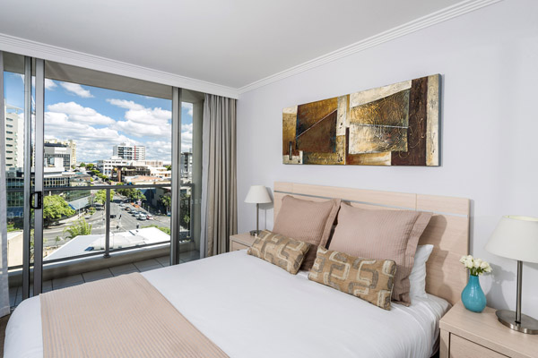 comfortable clean 1 bedroom Brisbane CBD Hotels apartment at Oaks Lexicon with balcony and blue summer skies outside