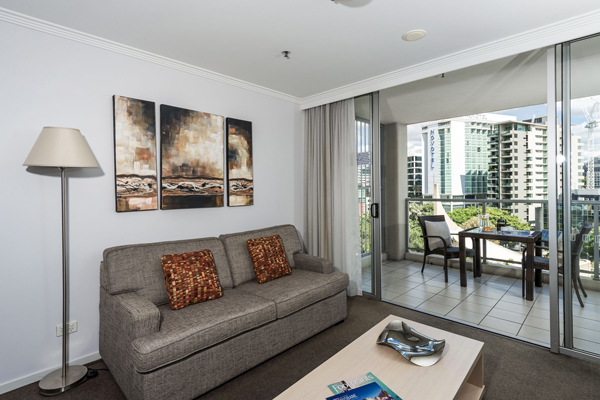 large couch in 1 bedroom apartment with sliding doors leading to balcony with views of Brisbane CBD at Oaks Lexicon Apartments