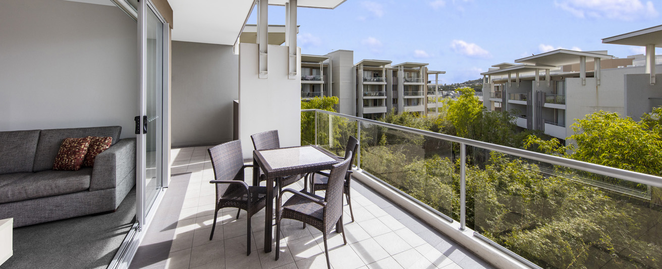 2 bedroom apartment balcony with table and chairs in Bowen Hills in Brisbane with trees in background