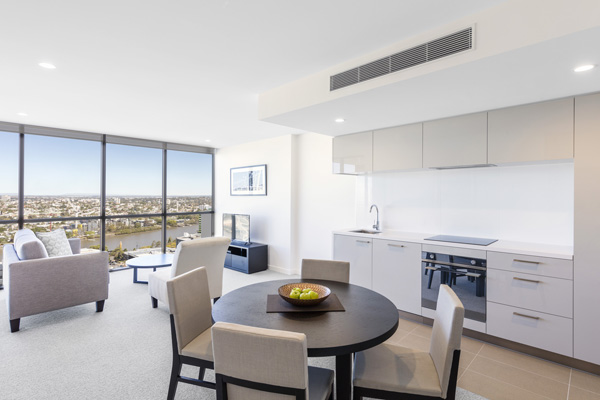 large living room area with comfortable furniture and big windows in 1 bedroom apartment at The Milton Brisbane hotel