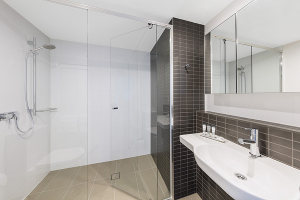 large shower with adjustable shower head in en suite bathroom of 2 bedroom executive apartment at The Milton Brisbane hotel