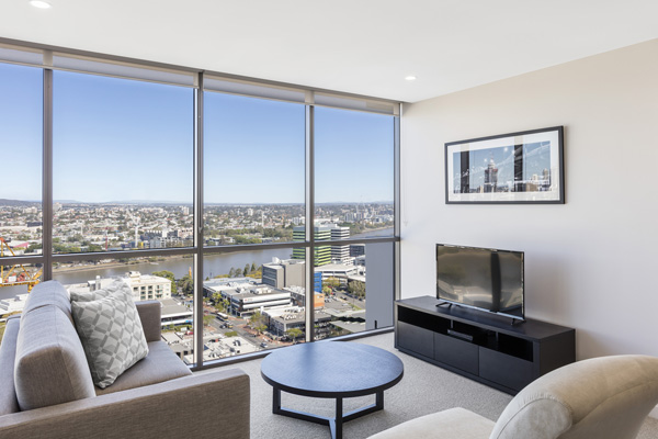 big living room with large windows and great views of Brisbane River at The Milton Brisbane hotel