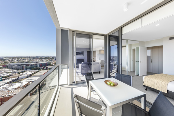 large 2 bedroom apartment balcony opposite Suncorp Stadium at The Milton Brisbane hotel with tables and chairs