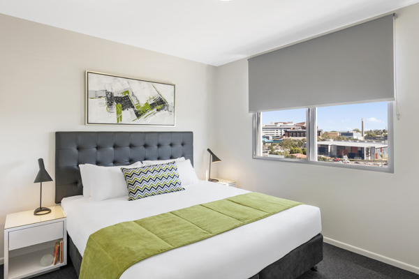 2 bedroom apartment with comfortable double bed and side lamps at Oaks Woolloongabba hotel Brisbane