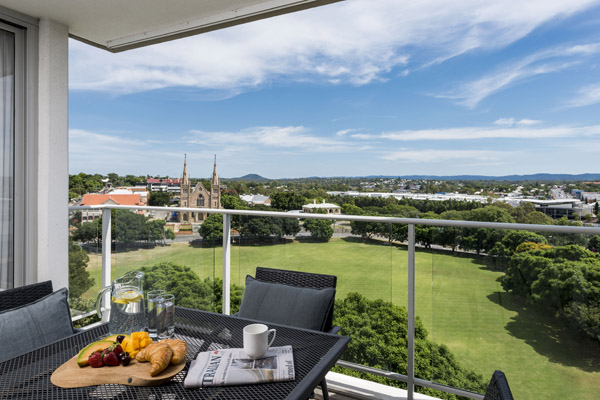 Hotels in Ipswich QLD with large 3 bedroom apartment balcony with furniture and view of park and cathedral in Ipswich, Queensland