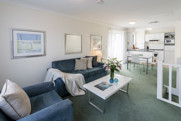large air conditioned living room with comfortable furniture, comfortable couches, tables and chairs in two bedroom apartment in Coolangatta