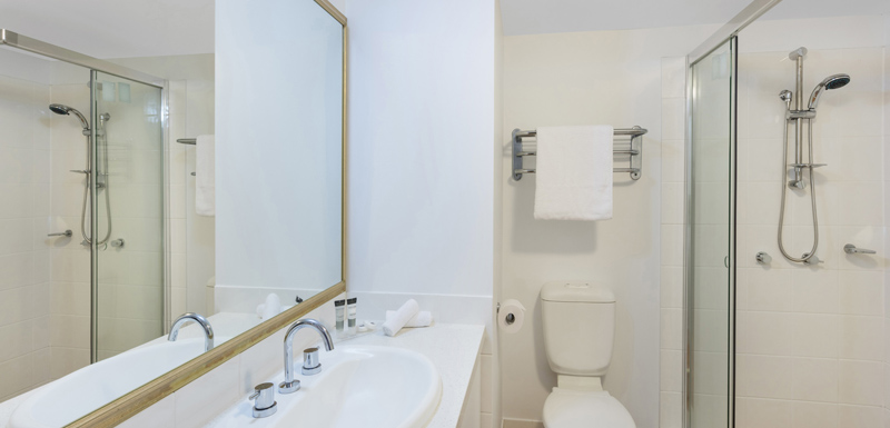 two bedroom hotel apartment en suite bathroom with toilet, adjustable shower and clean towels in Coolangatta