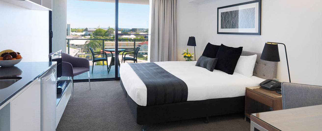 spacious air conditioned bedroom with balcony and views of Mackay at Oaks Carlyle hotel