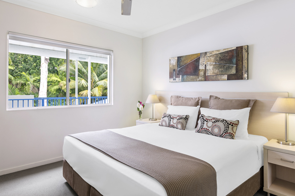 queen size bed with frsh pillows and clean sheets in 3 bedroom apartment at Oaks Lagoons hotel in Port Douglas, QLD, Australia