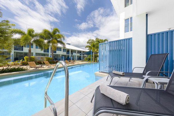 balcony with comfortable furniture leading to large swimming pool at Oaks Lagoons holiday resort in Port Douglas