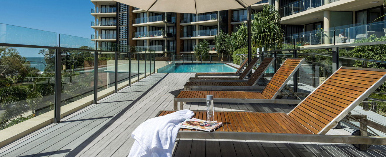 deck chairs and swimming pool outside during summer at oaks mon komo redcliffe hotel in Queensland, Australia