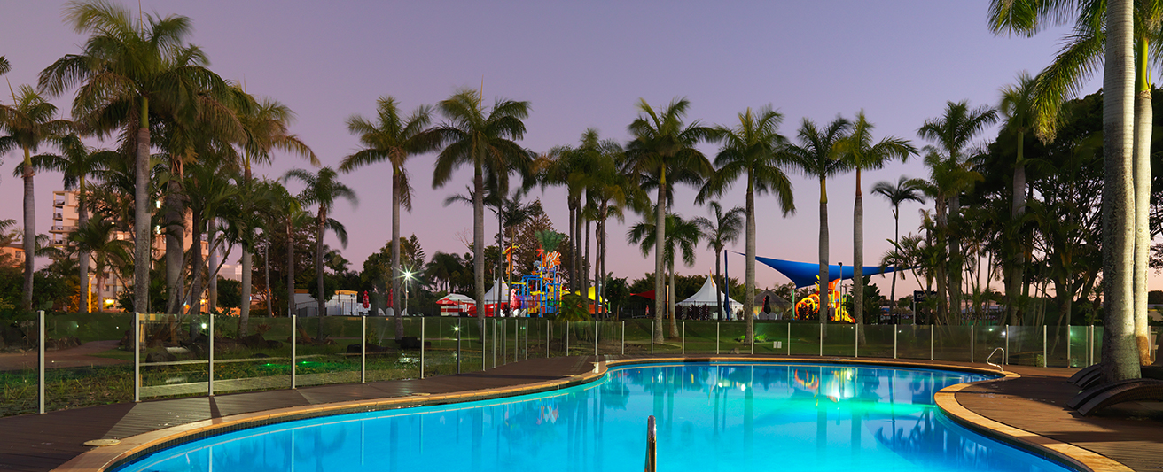 large outdoor swimming pool with palm trees and sun loungers at dusk Oaks Oasis Resort hotel in Caloundra, Sunshine Coast