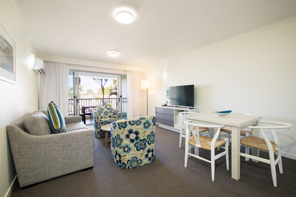 Caloundra hotels living room with TV and Foxtel in air conditioned one bedroom executive apartment ideal for corporate travellers visiting Sunshine Coast on business trips