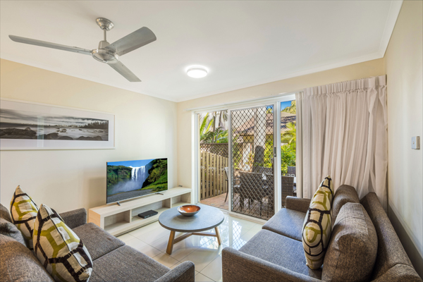 air conditioned living room with TV with Foxtel and comfortable couches in 3 bedroom hotel villa at Oaks Oasis Resort