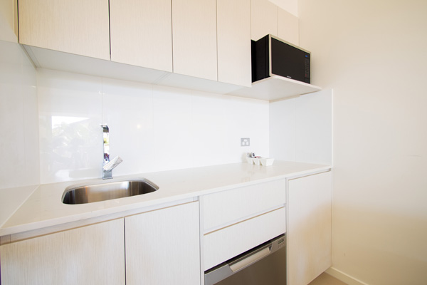 small kitchen with microwave, dishwasher, toaster and kettle in Executive King hotel room apartment at Oaks Oasis Resort in Caloundra