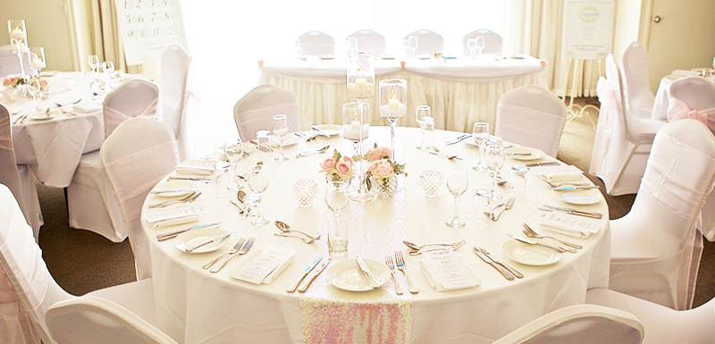 beautiful wedding table setting with cutlery and roses in vase in Caloundra on Sunshine Coast, Queensland, Australia