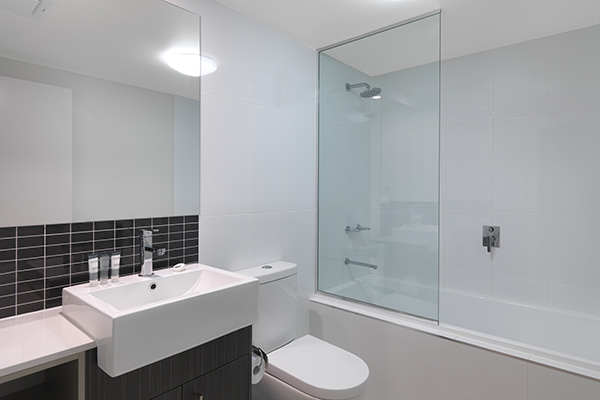 en suite bathroom of two bedroom apartment with big shower, bathtub and clean toilet at Oaks Rivermarque hotel in Mackay, Queensland, Australia