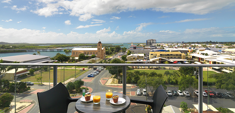 balcony with table and chairs and beautiful view of Mackay and Pioneer River at Oaks Rivermarque hotel