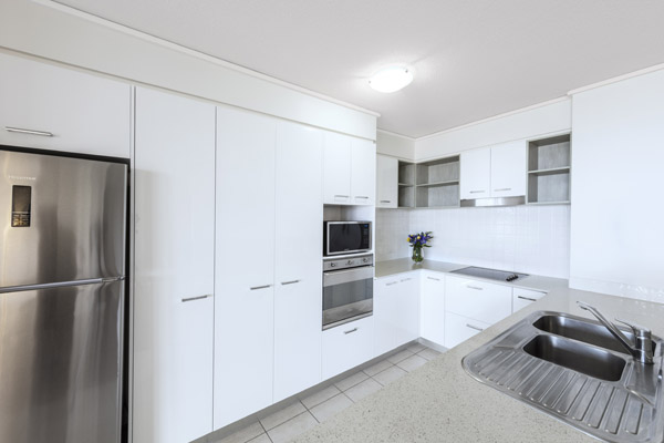 kitchen with large fridge, microwave, oven and kettle inair conditioned 3 bedroom apartment at Oaks Seaforth Resort hotel, Sunshine Coast, Queensland, Australia