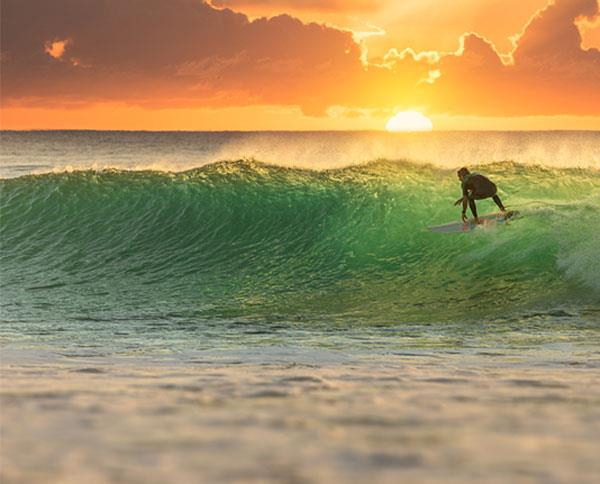 man surfing at sunset in Queensland with ocean in background