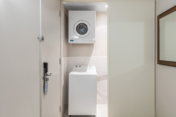 laundry room with washing machine and dryer for corporate travellers staying in 1 bedroom apartment near Adelaide Botanic Garden