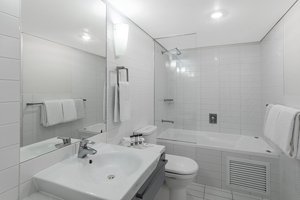 en suite bathroom of 1 bedroom apartment with large mirror, bath tub, shower, toilet and clean towels