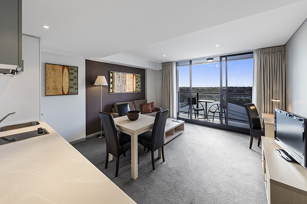 large air conditioned living room opening to private balcony with views of Adelaide Oval and Karrawirra Parri river