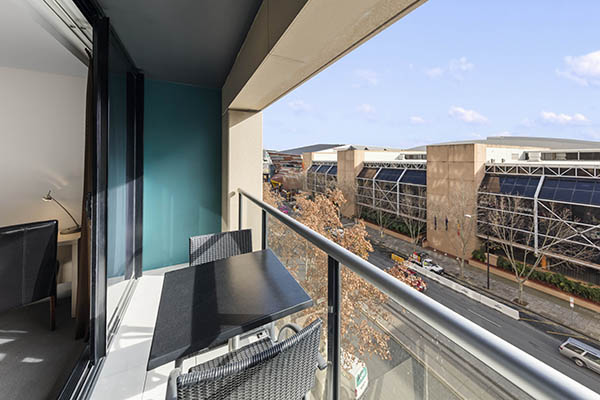 2 bedroom deluxe hotel room balcony with table and chairs and glass sliding doors leading to living room with blue sky and view of Adelaide CBD