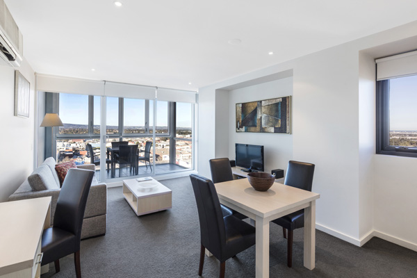 living room with couches, TV and private balcony in one bedroom apartment at iStay Precinct hotel on Morphett St in Adelaide city