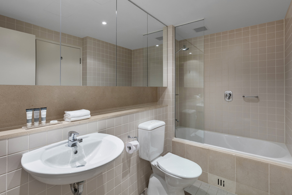clean en suite bathroom with shower, bath tub, toilet and large mirror in 1 bedroom apartment at Oaks Plaza Pier hotel in Glenelg, South Australia