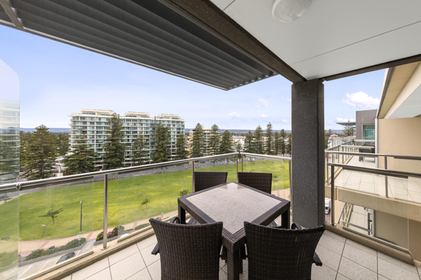 large balcony with tables and chairs and views of park at beach front hotel in Glenelg, South Australia