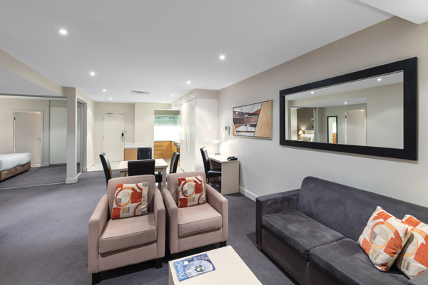 interior view of living room in 2 Bedroom Apartment with modern furniture and kitchen at Oaks Plaza Pier hotel on Glenelg beach