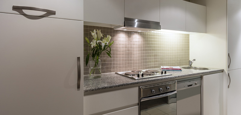 kitchen with large fridge, microwave, oven, hot plates for cooking and air con in 3 bedroom apartment at Oaks Plaza Pier hotel in Glenelg, South Australia