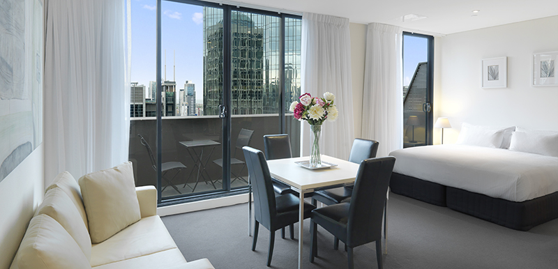 large hotel studio apartment with private balcony, couches, Wi-Fi and air con at Oaks on Collins in Melbourne city, Victoria, Australia