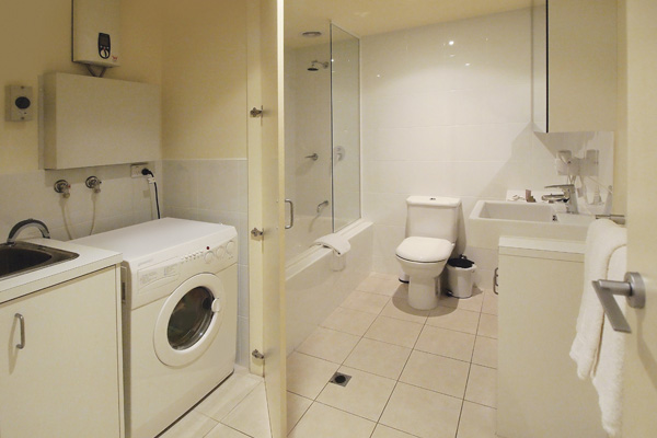 clean en suite bathroom with shower bath tub toilet fresh towels and laundry - Apartment Bathroom