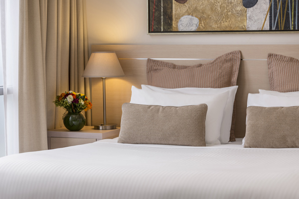 close up view of comfortable pillows on clean white sheets of double bed in Studio Apartment at Oaks On Lonsdale hotel in Melbourne city, Victoria, Australia