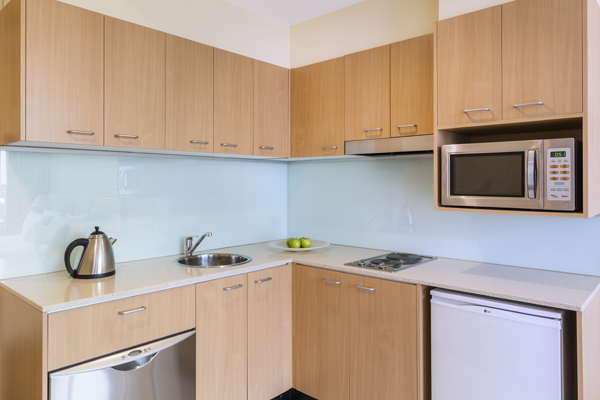 kitchenette with kettle, dishwasher, cutlery, bar fridge, microwave and stove hot plate for cooking in Studio Apartment at Oaks On Lonsdale hotel in Melbourne city, Victoria, Australia