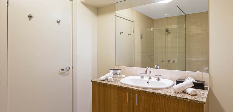 en suite bathroom with large mirrors, shower, bath tub and clean towels in 1 Bedroom Apartment at Oaks on Market hotel in Melbourne city, Victoria, Australia
